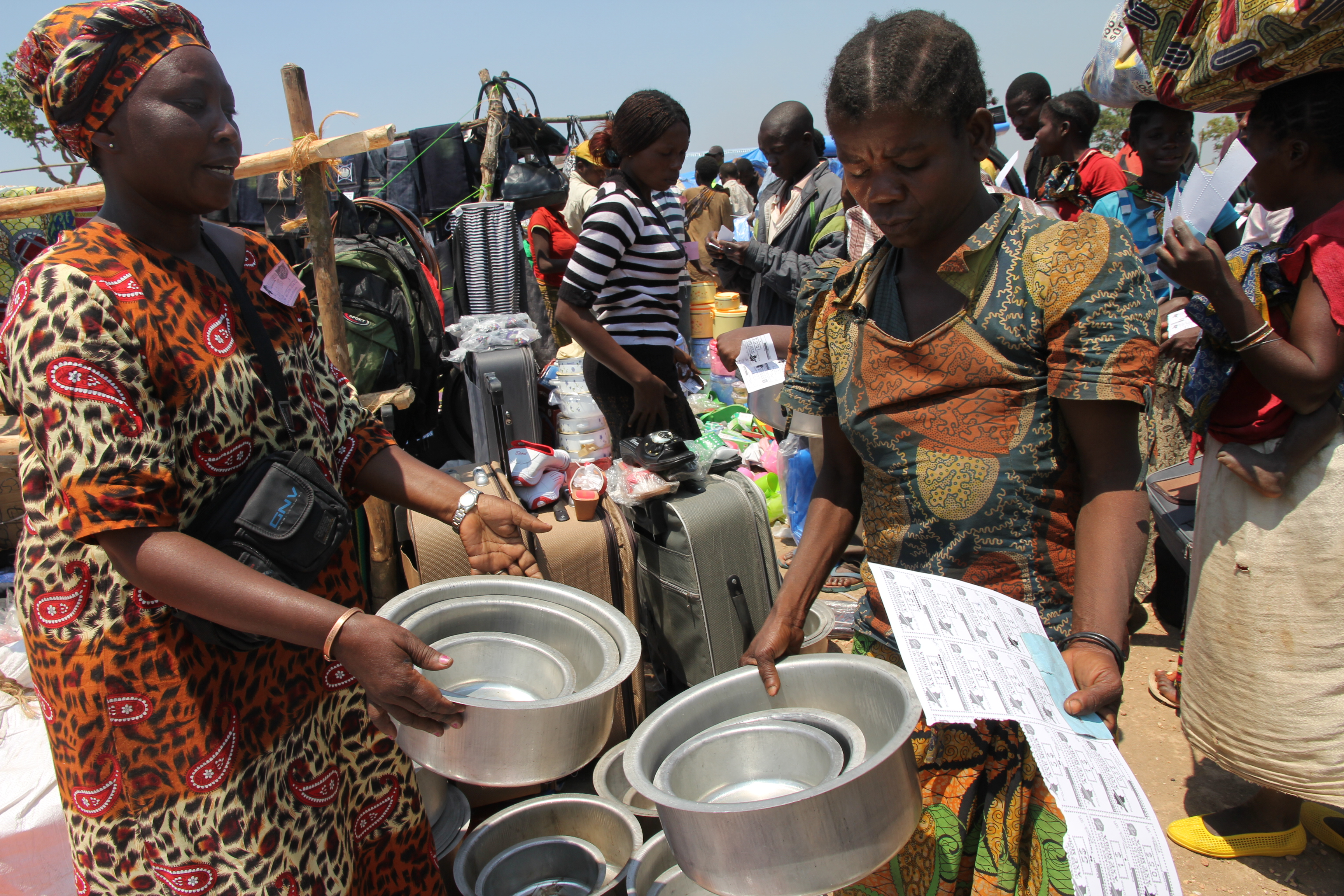 September 2013. Katanga, DRC. Jeanne Kaubwa presents a vendor with vouchers, part of an innovative 'IDP fair' system for distributing goods to displaced families in Kambilo camp.